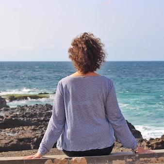 Eenzaam vrouwtje zittend op een rots en genietend van het prachtige uitzicht over de zee