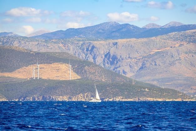 Eenzaam zeiljacht op zonnige zomerdag en de heuvelachtige kust met windmolenparken