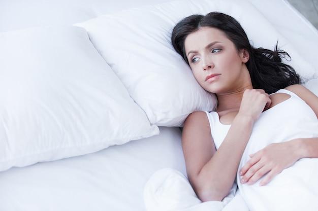 Eenzaamheid. depressieve jonge vrouwen die op het bed liggen en op een leeg kussen kijken