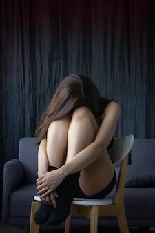 Eenzaamheid vrouw zit met haar knieën gebogen op houten stoel, boos en stress emotie
