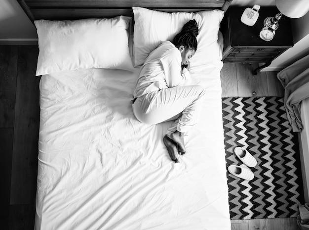 Eenzame afrikaanse amerikaanse vrouw op bed die alleen slapen