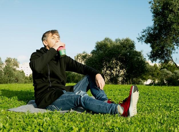 Eenzame, alleenstaande man van middelbare leeftijd die koffie drinkt in het park. concept van eenzaamheid, sociale afstand en zelfinsaltion. geestelijk gezondheidsconcept, verbinding maken met de natuur
