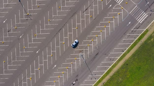 Eenzame auto rijdt op enorme lege parkeerplaats met veel lege parkeerplaatsen