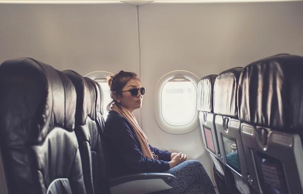 Eenzame aziatische vrouwenzitting naast het gebruik van het vliegtuigvenster voor reizend thema