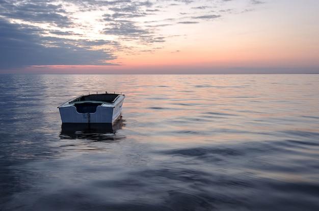 Eenzame boot op de zee bij zonsondergang