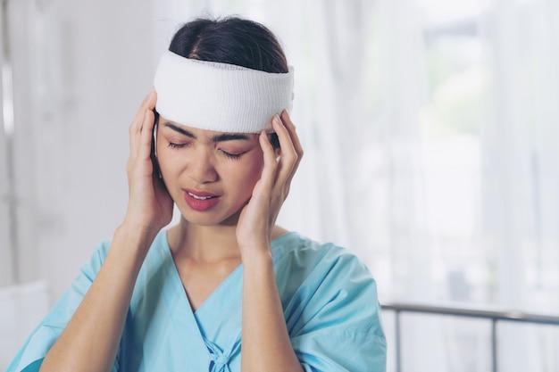 Eenzame de verwondingshoofdpijnvrouw van ongevallenpatiënten in het ziekenhuis - medisch concept