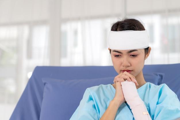 Eenzame de verwondingsvrouw van ongevallenpatiënten op het bed van de patiënt in het ziekenhuis wil naar huis gaan - medisch concept