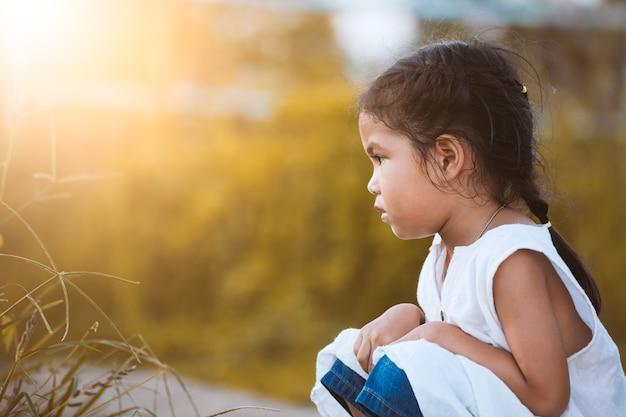 Eenzame en droevige meisjezitting in de weide in uitstekende kleurentoon