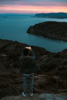 Eenzame figuur van toerist of reiziger die bovenop een klif of berg staat