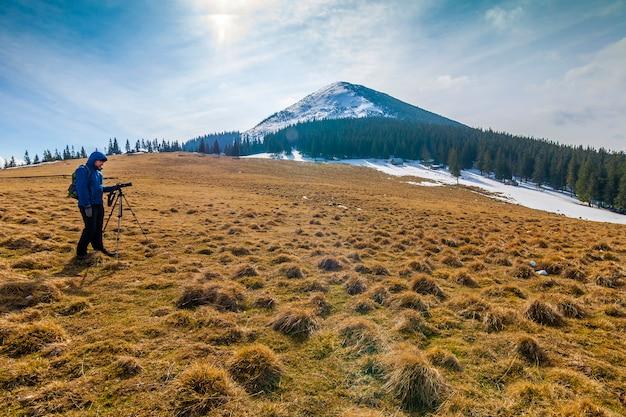 Eenzame fotograaf in de bergen met een camera op een statief bij koud weer