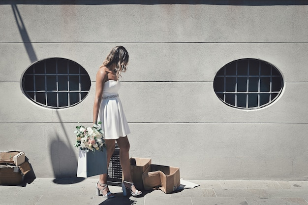 Eenzame, gefrustreerde bruid met een bruiloftsbloem die wanhopig rondloopt