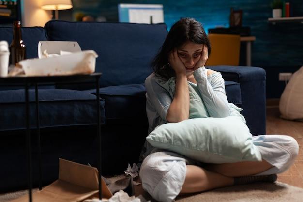 Eenzame getraumatiseerde gefrustreerde zieke vrouw die het hoofd in handen houdt en zich kwetsbaar voelt