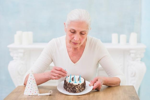 Eenzame hogere vrouw die kaarsen op verjaardagscake thuis schikken