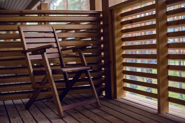 Eenzame houten stoel op het balkon van hout met schotten in de herfstdag