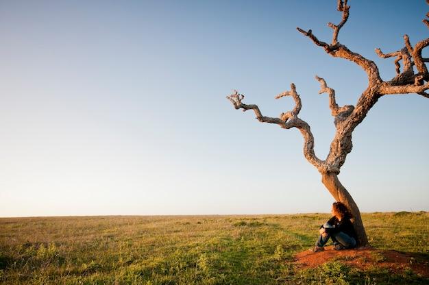 Eenzame jonge blanke vrouw zittend op een dode boombasis en een ontspannend concept voor mensen die genieten van de buitenaardse reizen en anders leven
