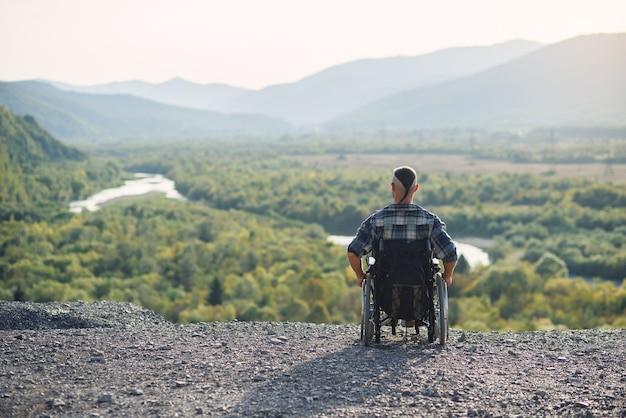 Eenzame jonge man in een rolstoel genieten van frisse lucht in zonnige dag op de berg