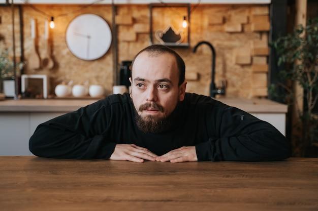 Eenzame jonge man met baard, verdrietig in depressie, op de tafel in de keuken, in huis, binnenshuis