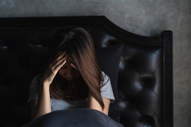 Eenzame jonge vrouw gedeprimeerd en beklemtoond zittend in de donkere slaapkamer, negatief emotieconcept