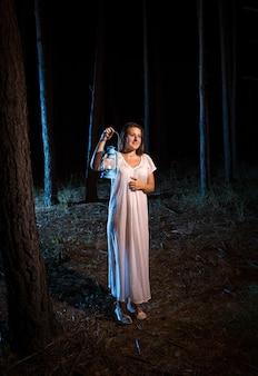 Eenzame jonge vrouw in nachtjapon wandelen in het bos 's nachts met gaslamp