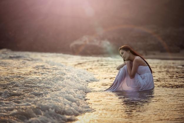 Eenzame jonge vrouw op het strand