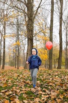 Eenzame jongen wandelen in het park in het herfstseizoen met een rode ballonnen in zijn vakantie