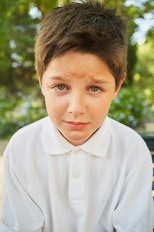 Eenzame jongen zit en huilt terwijl hij naar de camera kijkt