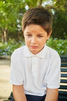 Eenzame jongen zittend en huilend op de bank