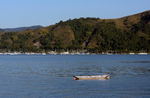 Eenzame kano op kalme zee, met boten, heuvel en blauwe lucht