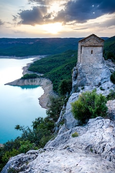 Eenzame kluis met uitzicht op het meer. rotsachtig landschap. la noguera, catalonië, canelles swamp