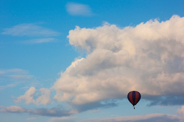 Eenzame lucht baloon die voor witte gezwollen wolken vliegt