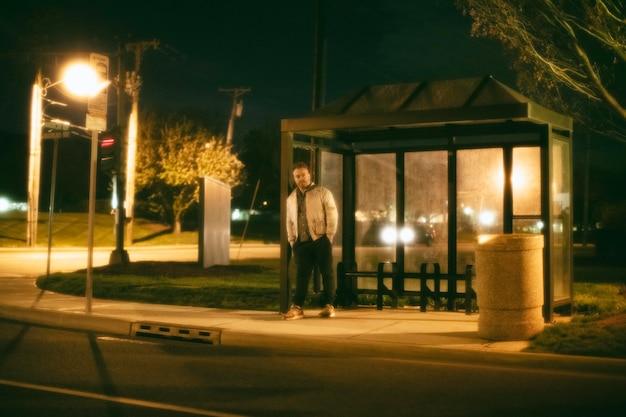 Eenzame man bij het busstation in de stad 's nachts