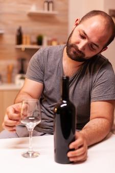 Eenzame man die naar een leeg glas wijn kijkt en teleurgesteld is?