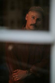 Eenzame man kijkt uit het raam tijdens zelfquarantaine vanwege de covid-19-pandemie in groot-brittannië.