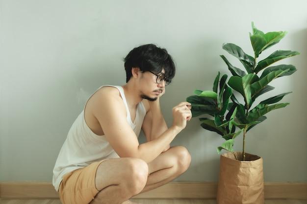 Eenzame man vriend met zijn boom plant in het appartement.