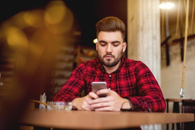 Eenzame man zit bij restaurant en sms'en.