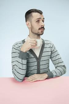 Eenzame man zit op roze studio en kijkt verdrietig met de kop koffie in de hand.