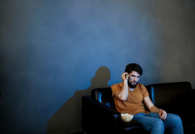 Eenzame man zittend op de bank met popcorn platen grijze muur