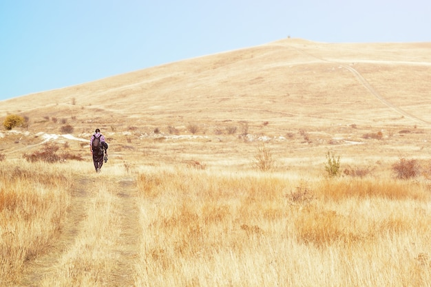 Eenzame mannelijke fotograaf loopt op de steppe aan de horizon, vakantie, reizen