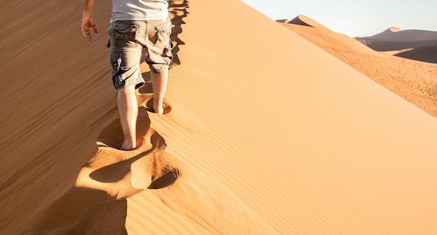 Eenzame mens die op zandkam lopen bij duin 45 in sossusvlei-woestijn in namibië
