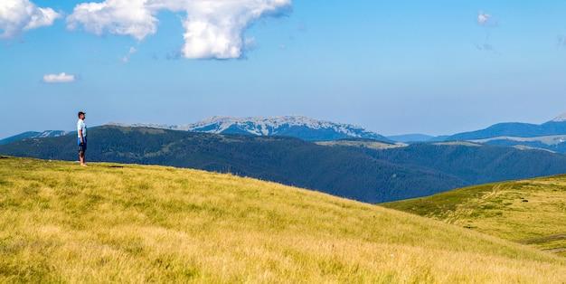 Eenzame mensenwandelaar die zich op een brede heuvel enjoing bergmening bevindt