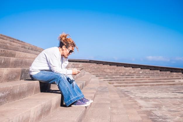 Eenzame middelbare leeftijd vrouw aan het werk met een smartphone zittend op een lange mooie staris in stedelijke wedstrijd. vrije tijd met technisch concept voor moderne dame verbonden met vrienden of zakelijk team