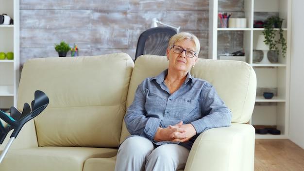 Eenzame oude vrouw die op de bank zit in een verpleeghuis en de handen bij elkaar houdt