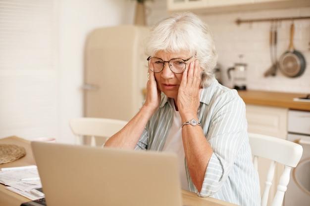Eenzame, overstuur gepensioneerde vrouw met grijs haar met gefrustreerde gestreste blik, hoofd aanraken, financiële problemen onder ogen zien, geld proberen te besparen om al haar schulden af te betalen, uitgaven berekenen, laptop gebruiken