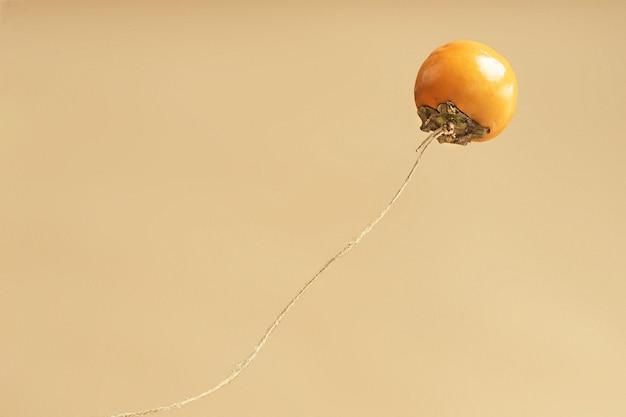 Eenzame persimmon vliegt op een beige achtergrond met een kopie van de ruimte.