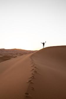 Eenzame persoon die op de top van een zandduin in een woestijn staat bij zonsondergang