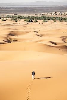 Eenzame persoon die op een zonnige dag in een woestijn in de buurt van zandduinen loopt