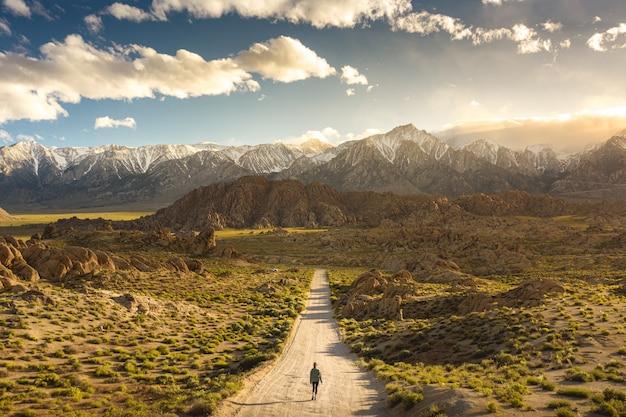 Eenzame persoon lopen op een pad in de heuvels van alabama in californië met mount whitney