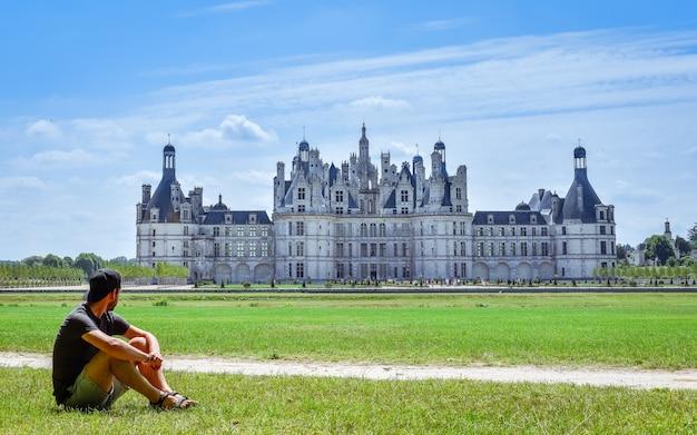 Eenzame reiziger op een zonnige dag die in juli naar het kasteel van chambord, frankrijk kijkt