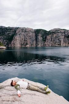 Eenzame reizigersmens die op steen van fjord in noorwegen liggen.