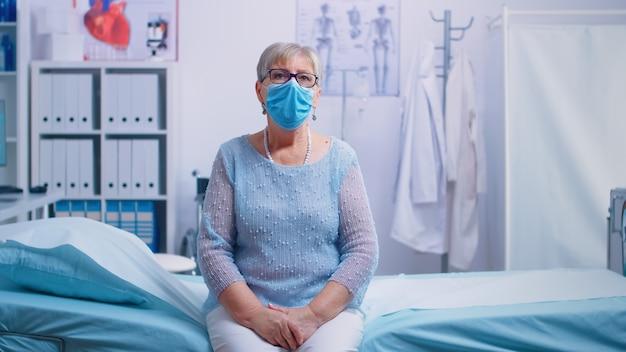 Eenzame senior vrouw in ziekenhuisbed met een beschermend masker, wachtend op het resultaat van het coronavirus. wereldwijde gezondheidscrisis, medisch systeem tijdens pandemie, zieke oudere patiënt in privéziekenhuis of kliniek
